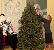Елена Полянская, заведующая музеем И.С. Тургенева, загадывает желание, завязывая на елке ленточку открытия.